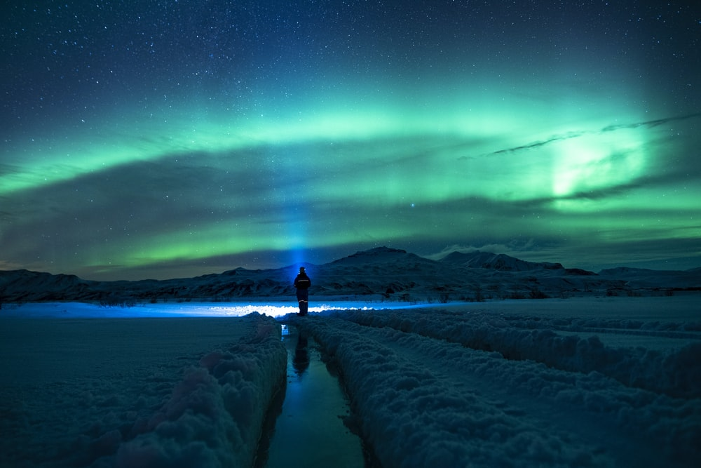 person standing on snow covered ground under green sky