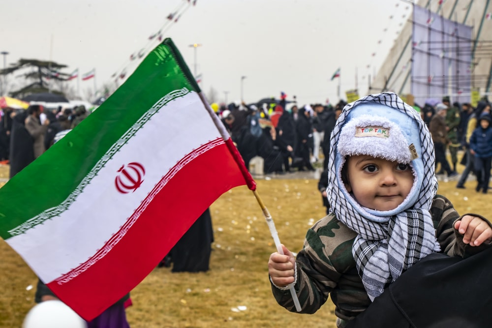 child in black and white jacket holding green and white flag