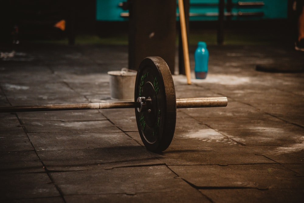 black and blue dumbbell on brown wooden floor