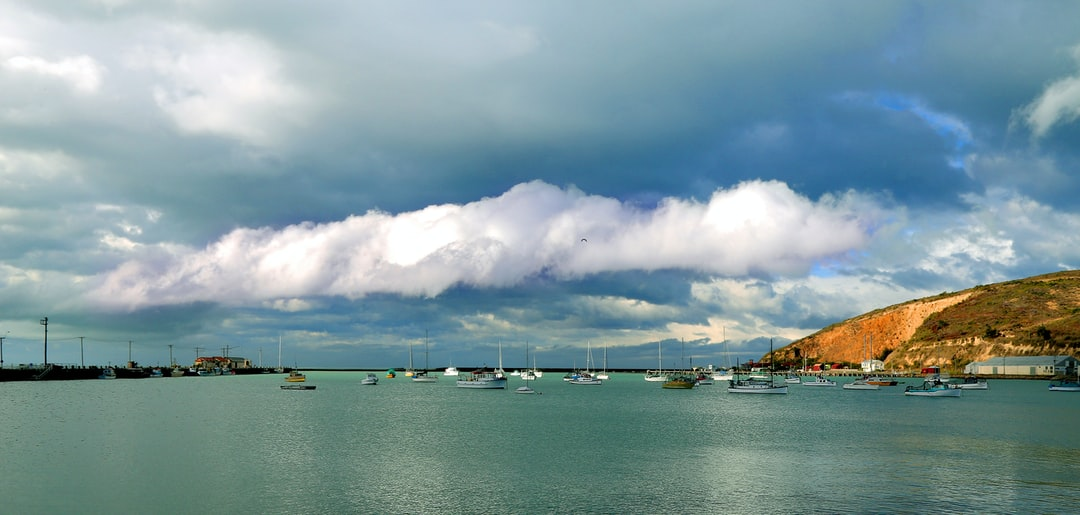 harbor,bay,peaceful,cliff,rolling cloudform,boats,breakwater,calm,safe,fishing vessels,