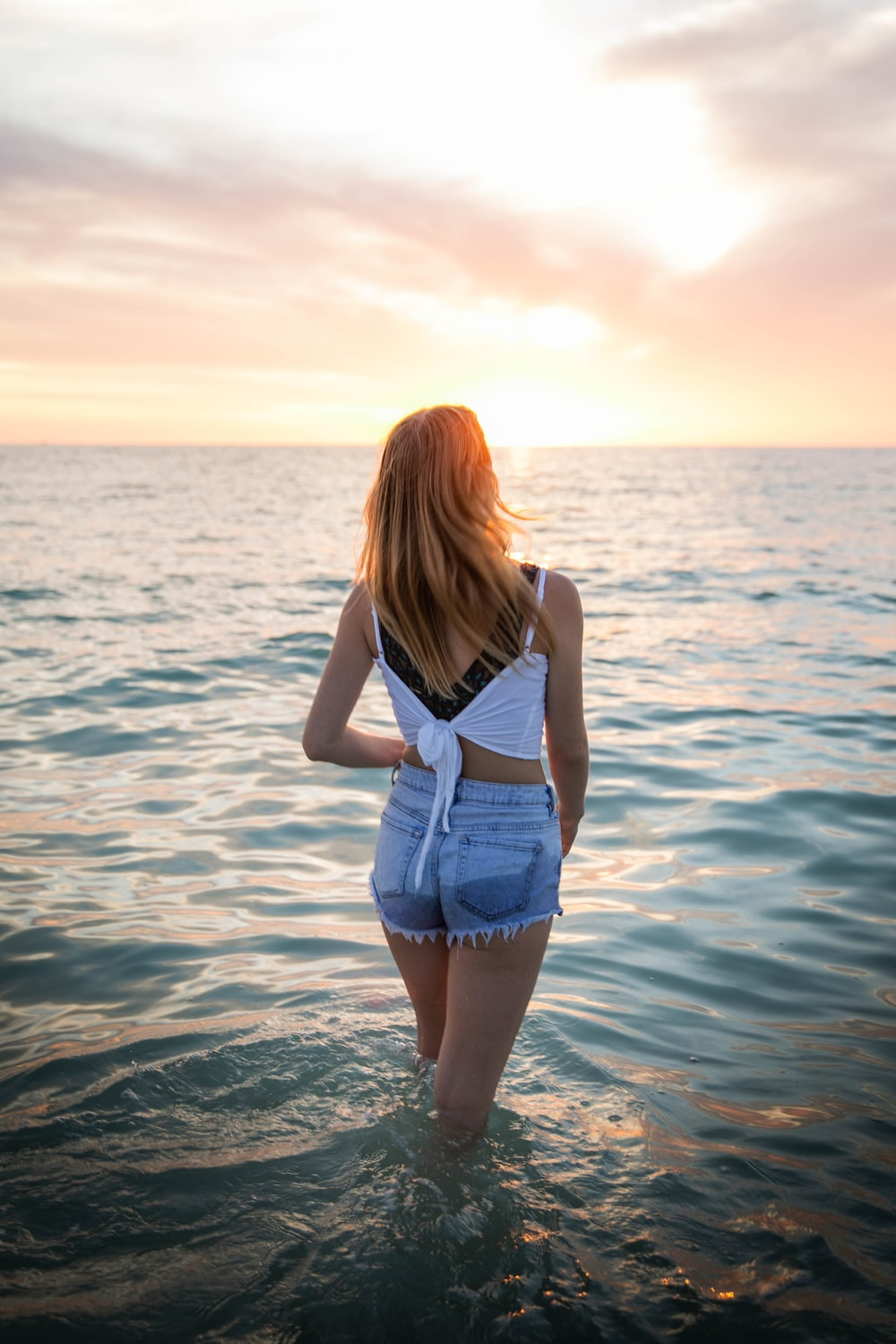 woman in white tank top and blue denim shorts standing on water during daytime
