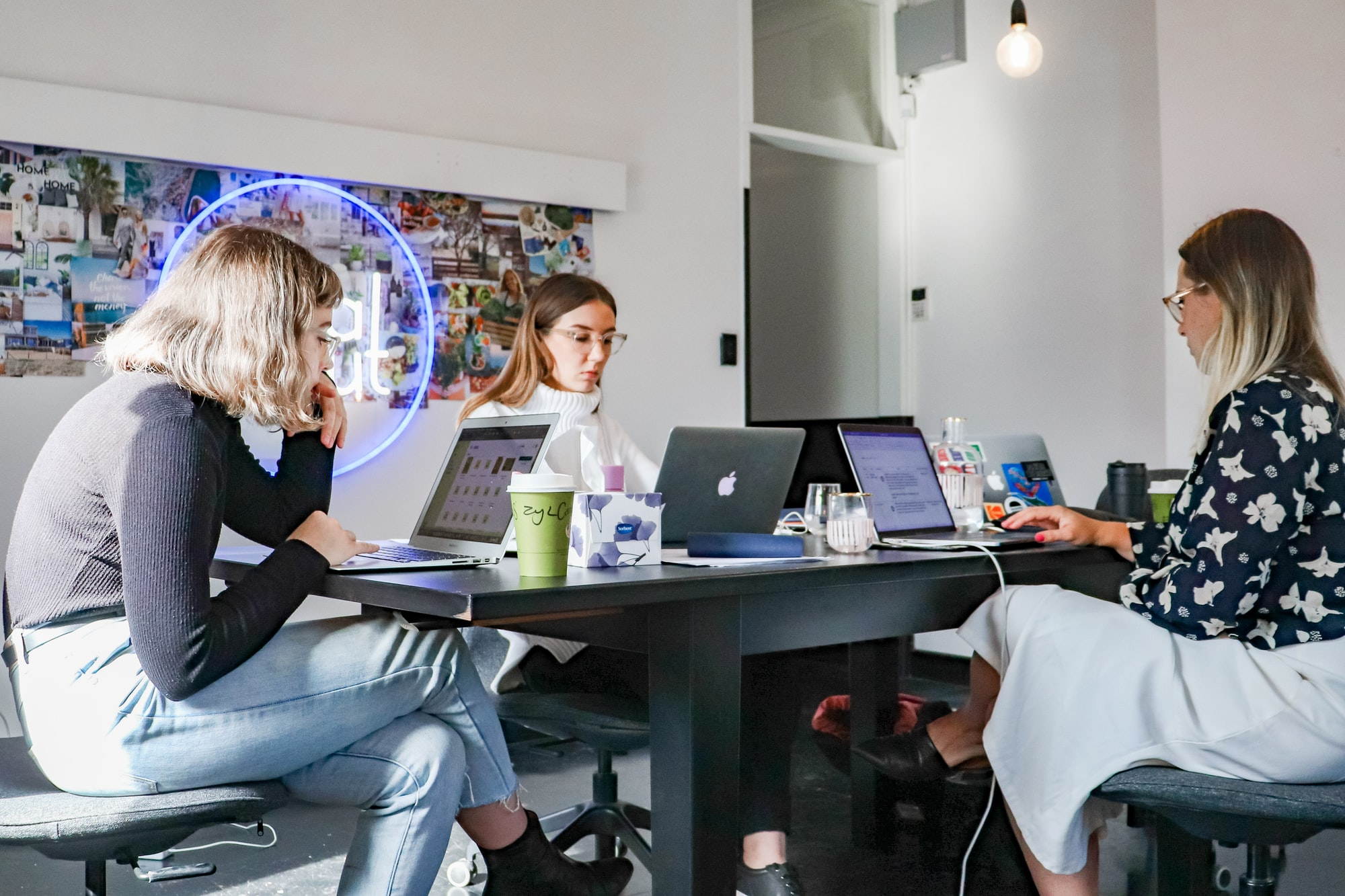 Three Gen Z females sitting at a shared desk, working on their laptops.