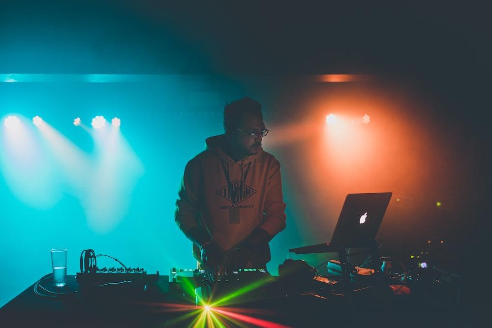 man in brown hoodie standing in front of macbook pro