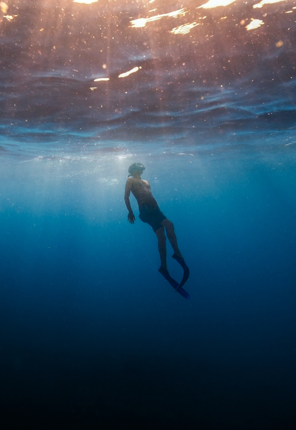 man in black shorts swimming under water