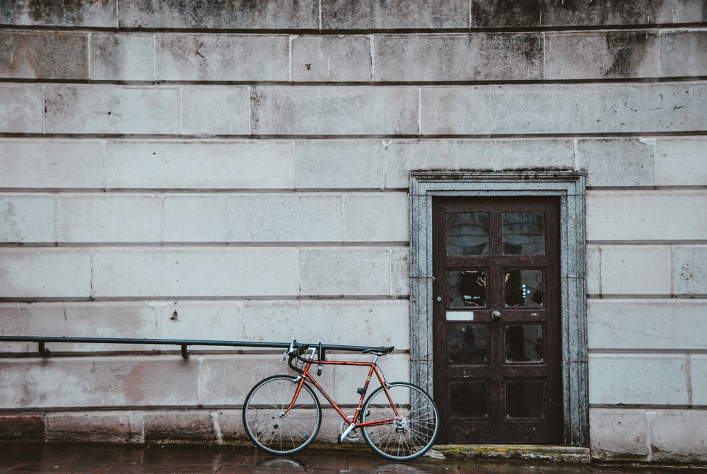 red city bike parked beside gray concrete wall