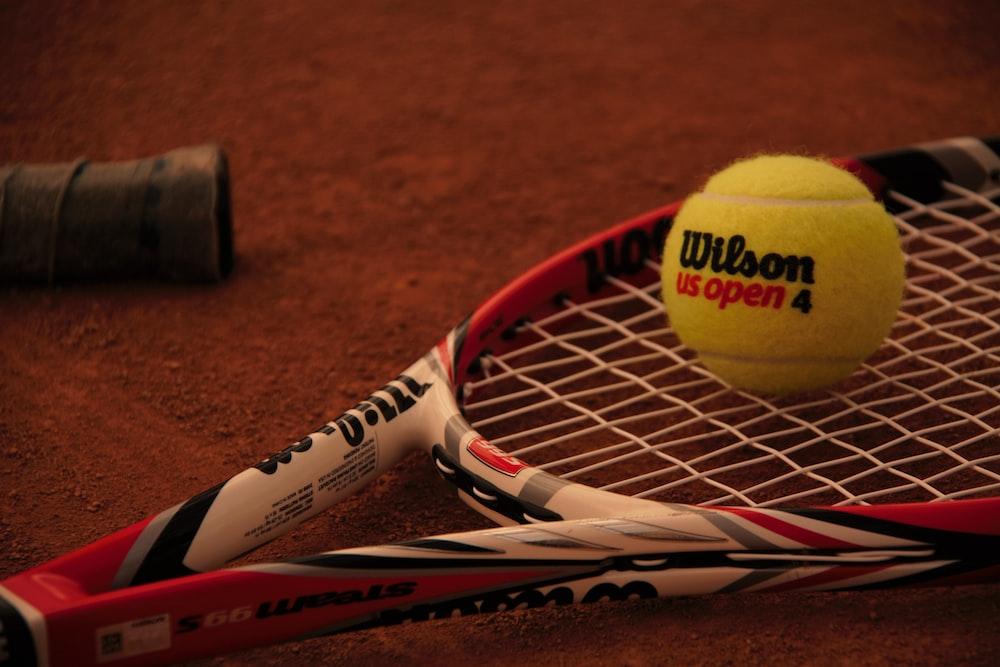 green tennis ball beside tennis racket