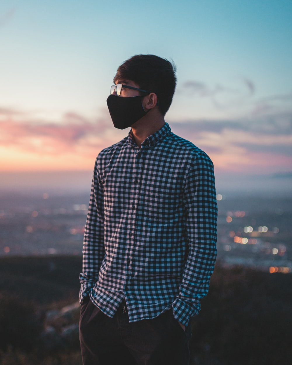 man in blue and white checkered dress shirt wearing black sunglasses during sunset