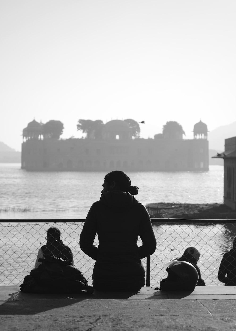 man in black jacket and black backpack standing beside black metal fence during daytime