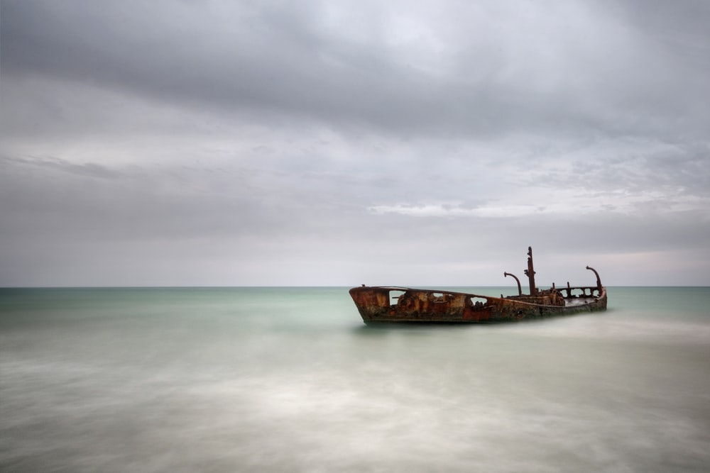 brown ship on sea under cloudy sky during daytime