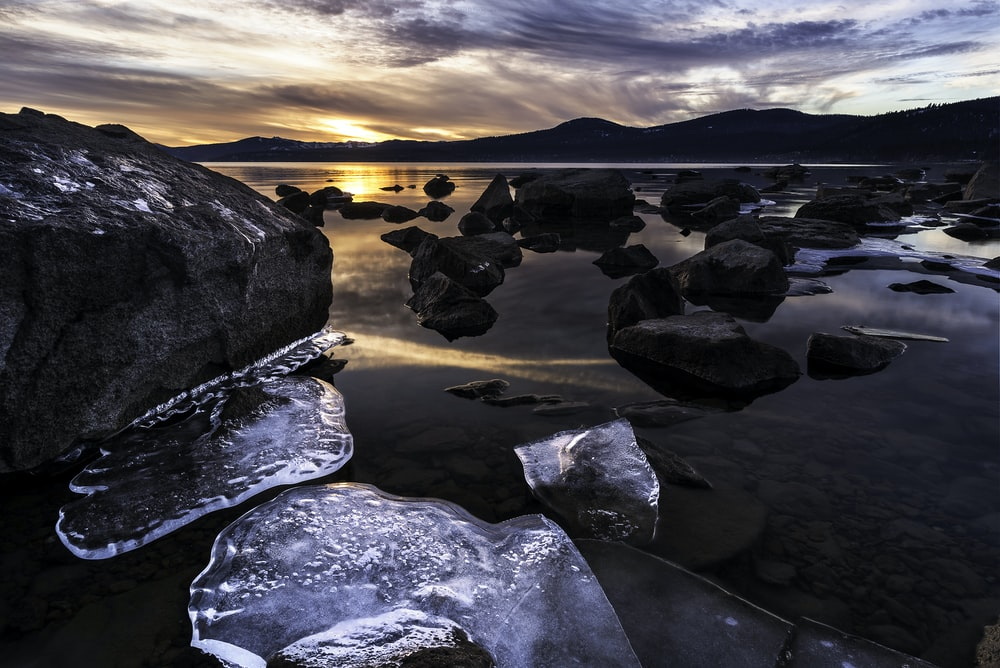 gray rocks on body of water during sunset