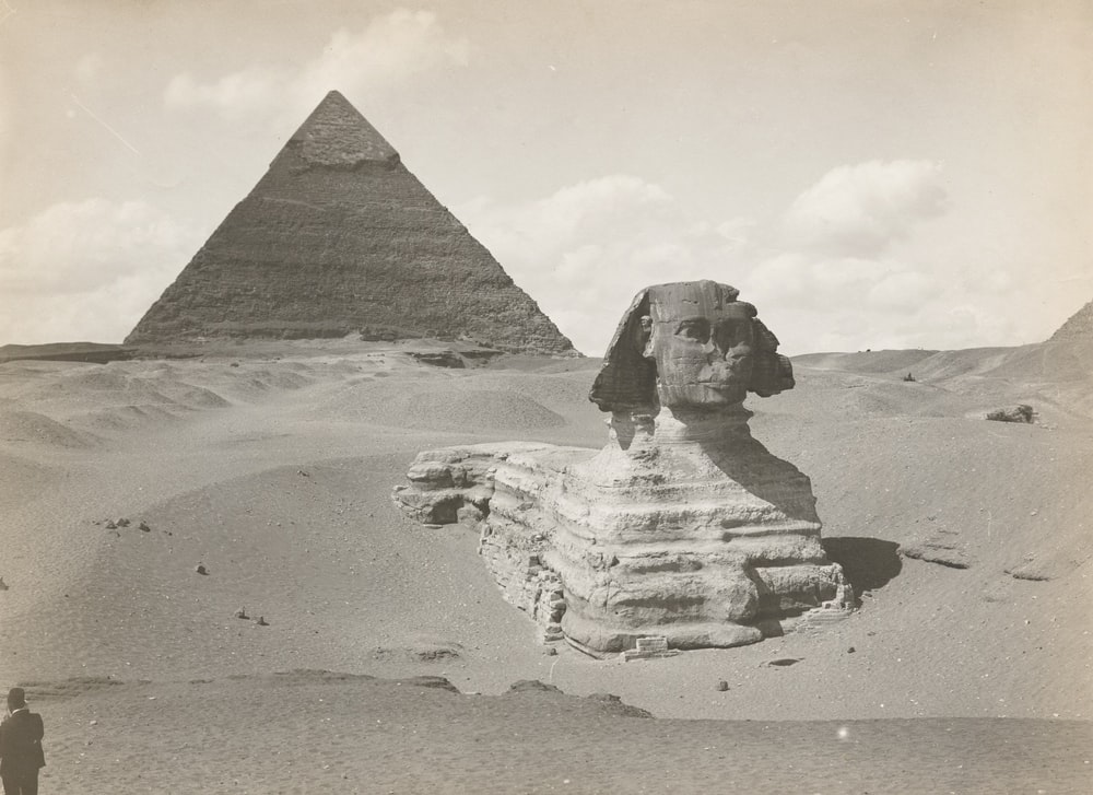 grayscale photo of pyramid on sand