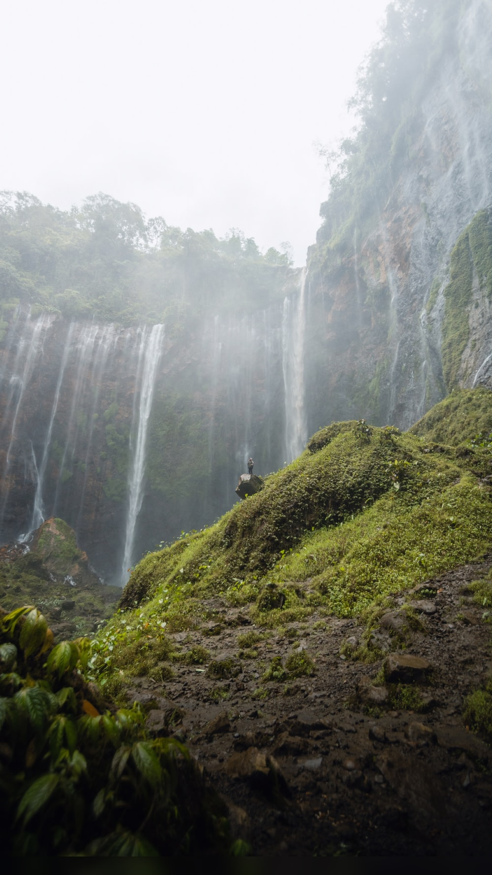 waterfalls in the middle of green grass covered mountain