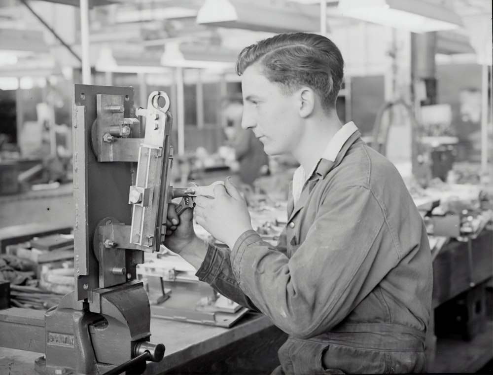 man in gray jacket holding a machine