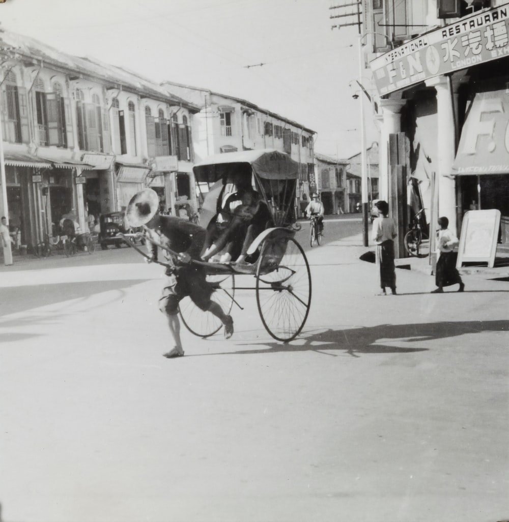grayscale photo of man riding on horse carriage in the street
