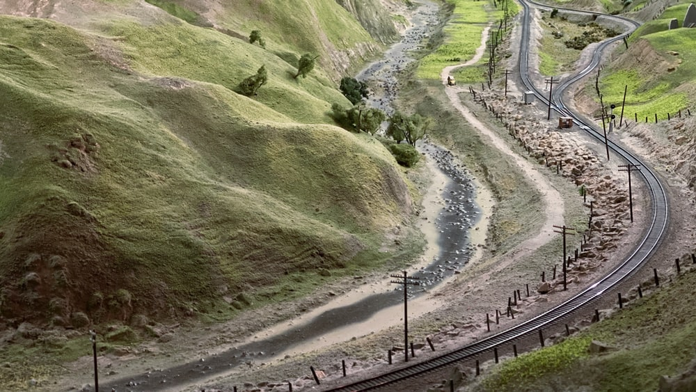 green grass field and train rail