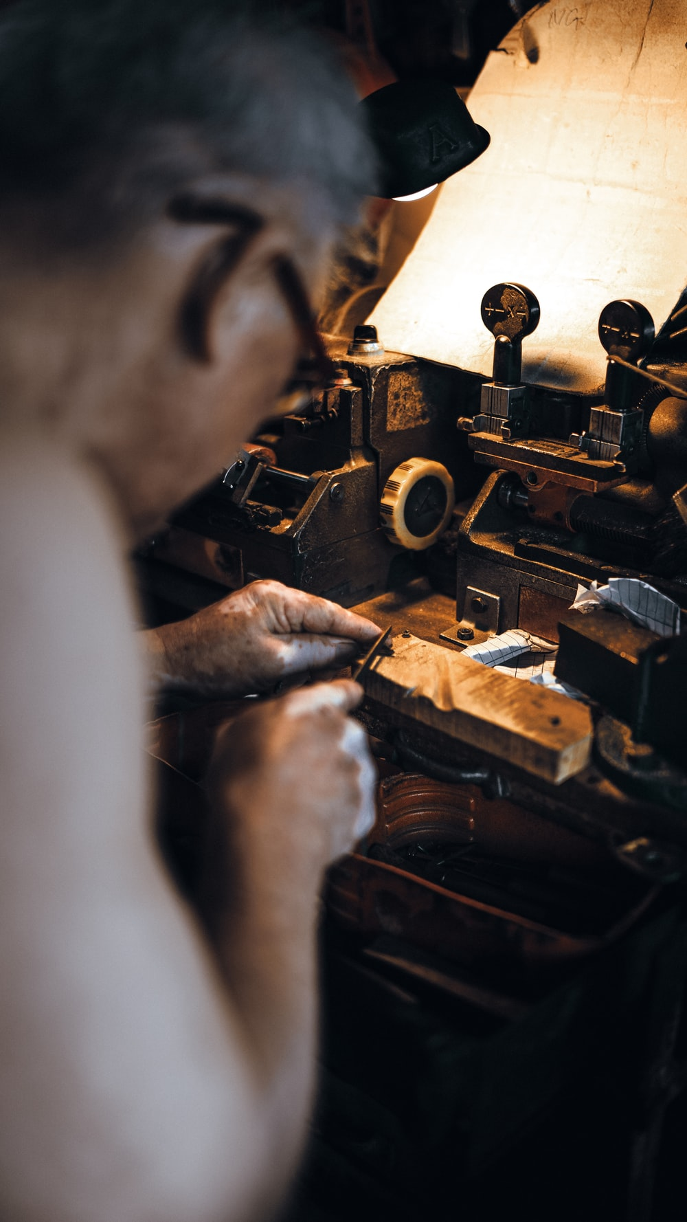 person in gray long sleeve shirt using brown sewing machine
