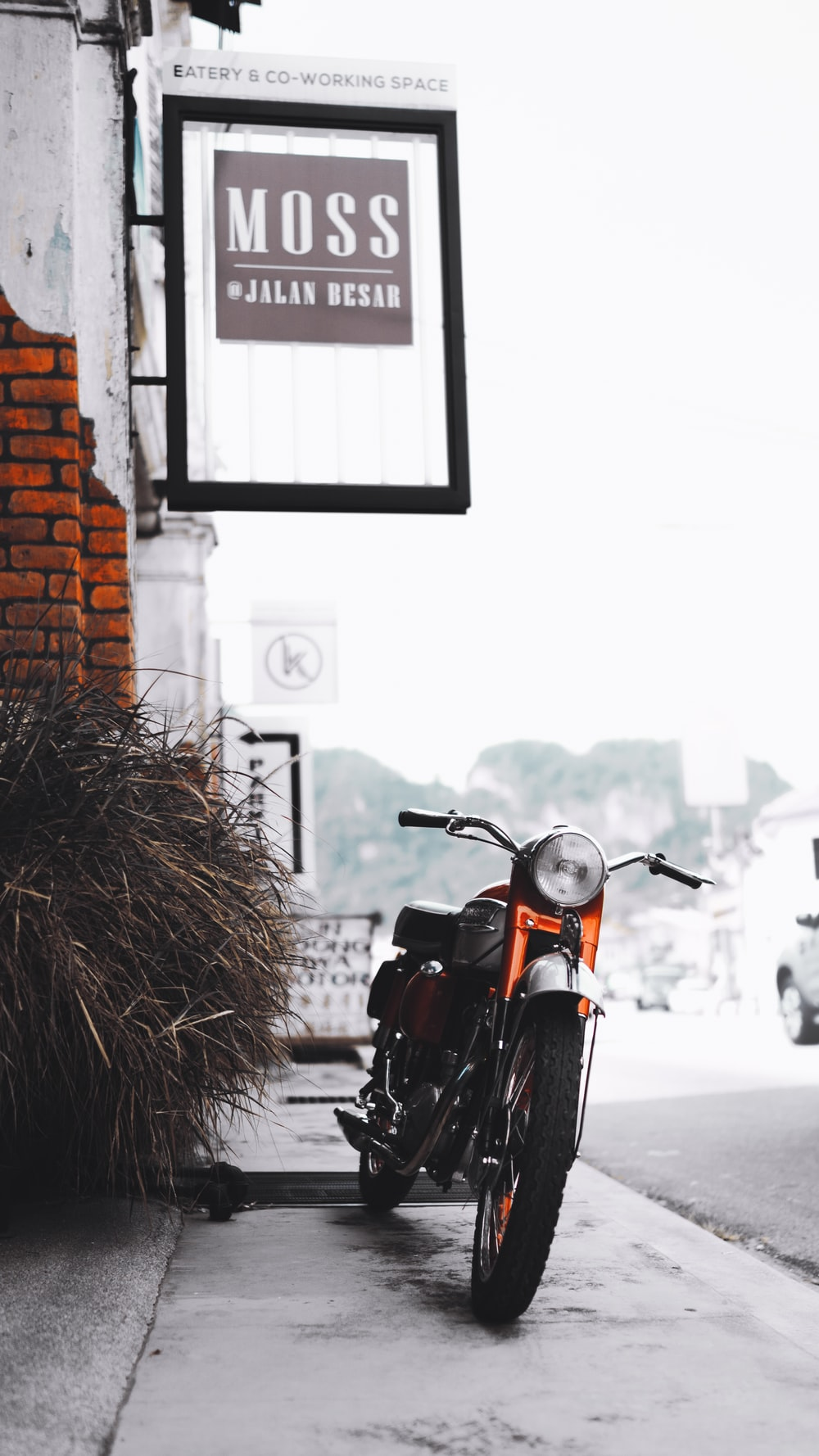 red and black motorcycle parked beside brown brick wall during daytime