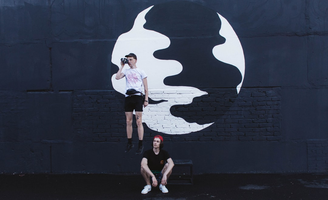Woman In White T-Shirt and Black Shorts Standing Beside Wall With Graffiti - unsplash