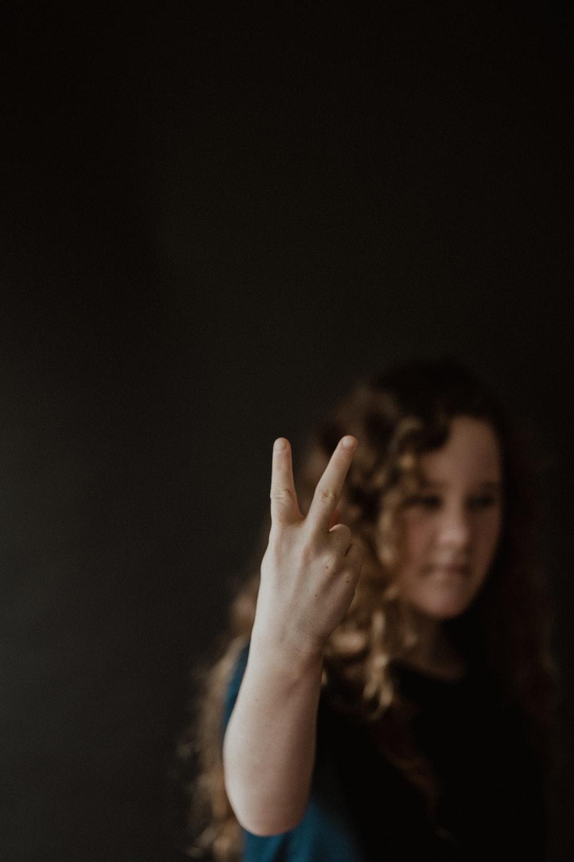woman in blue shirt raising her hand