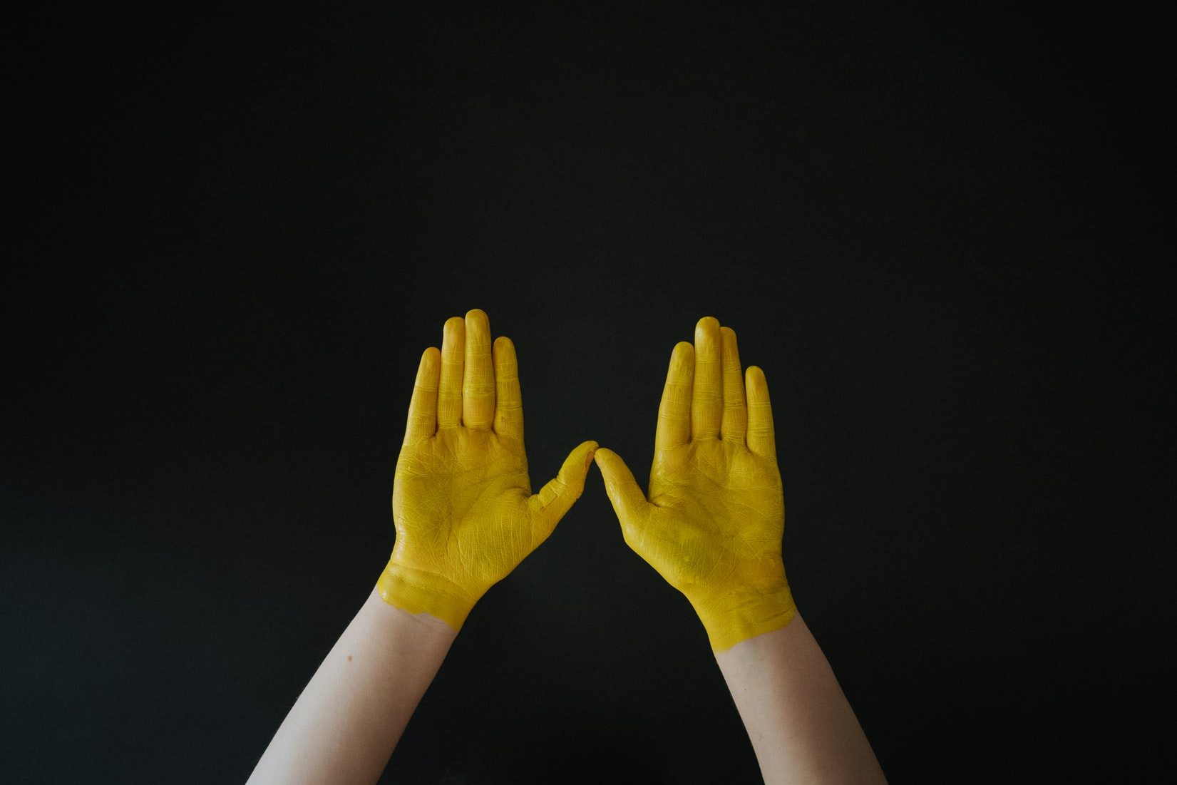 hands painted yellow on a black background