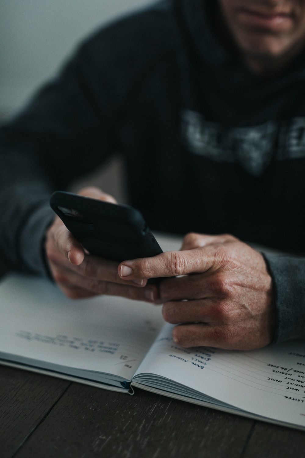person holding black smartphone on white paper