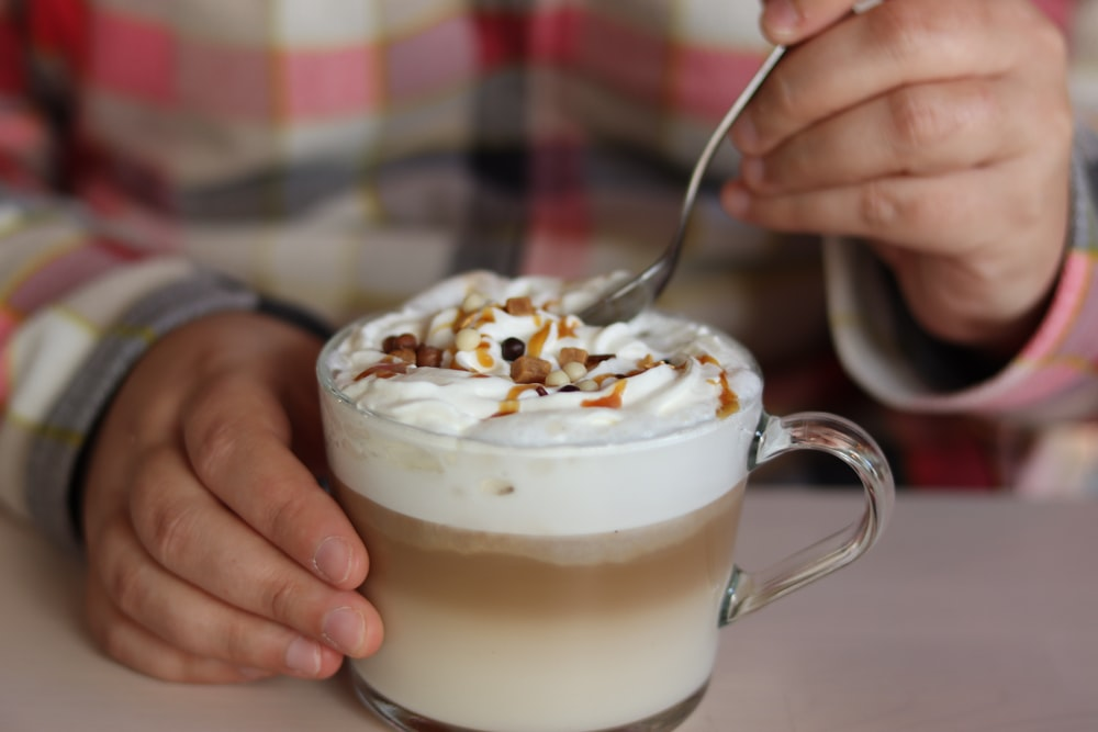 person holding ice cream with white cream on clear glass mug