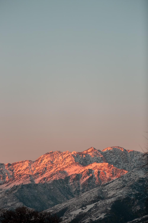 brown rocky mountain under gray sky