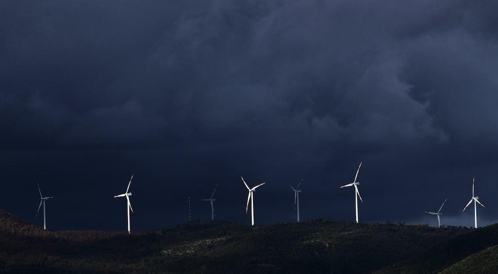 wind turbines on hill under gray sky