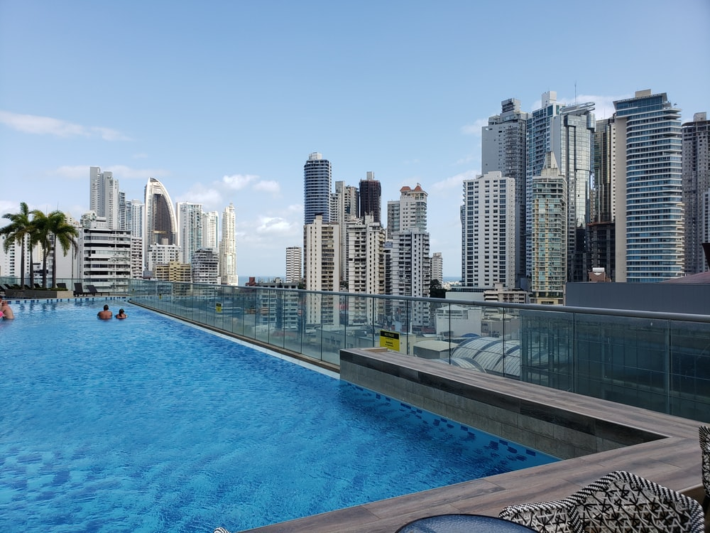 blue swimming pool near city buildings during daytime