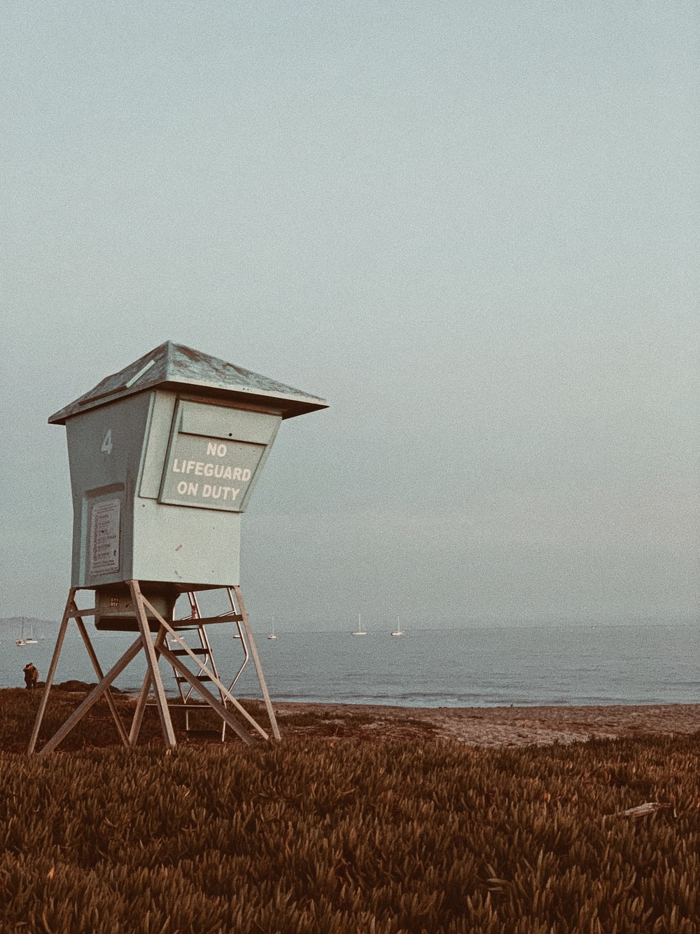 white wooden lifeguard house on brown field under white sky during daytime