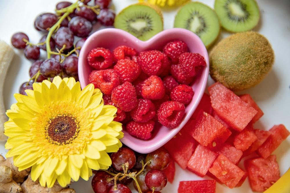 strawberries and yellow sunflower in white ceramic bowl