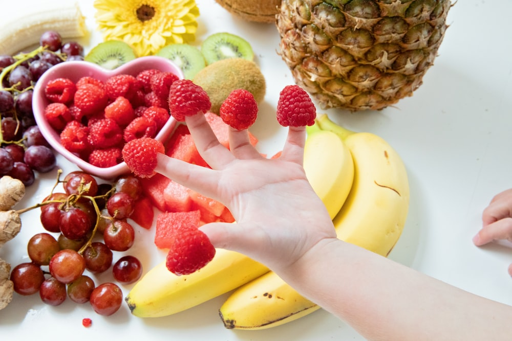 person holding a ripe banana and strawberries
