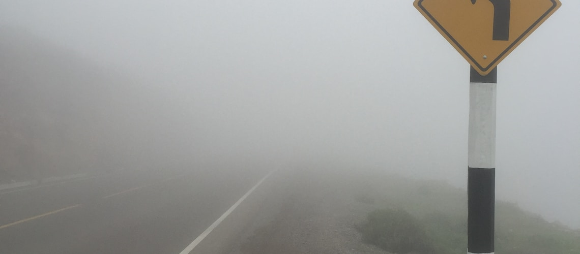 black and yellow road sign on foggy weather