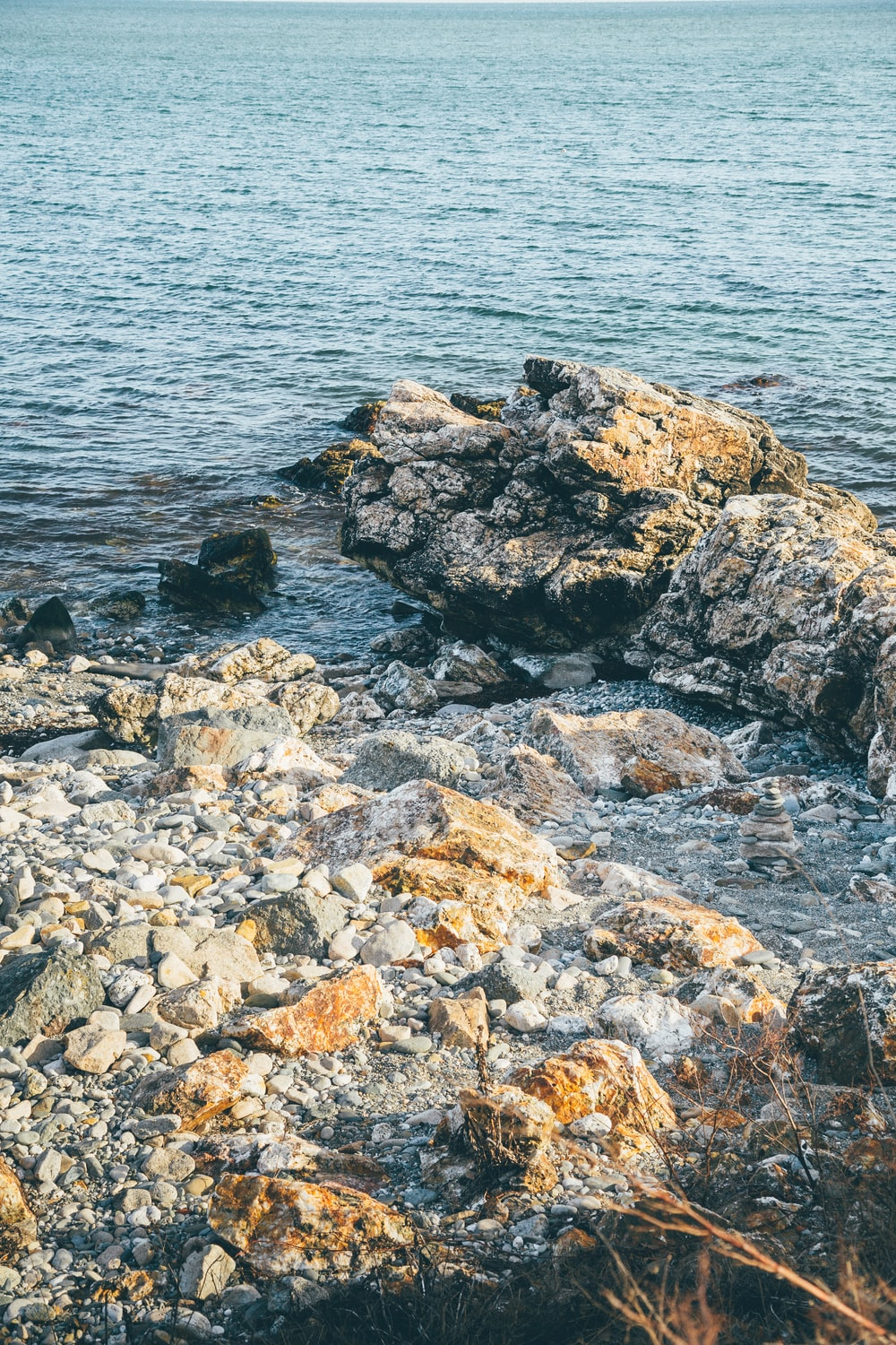 gray and brown rocks beside body of water during daytime