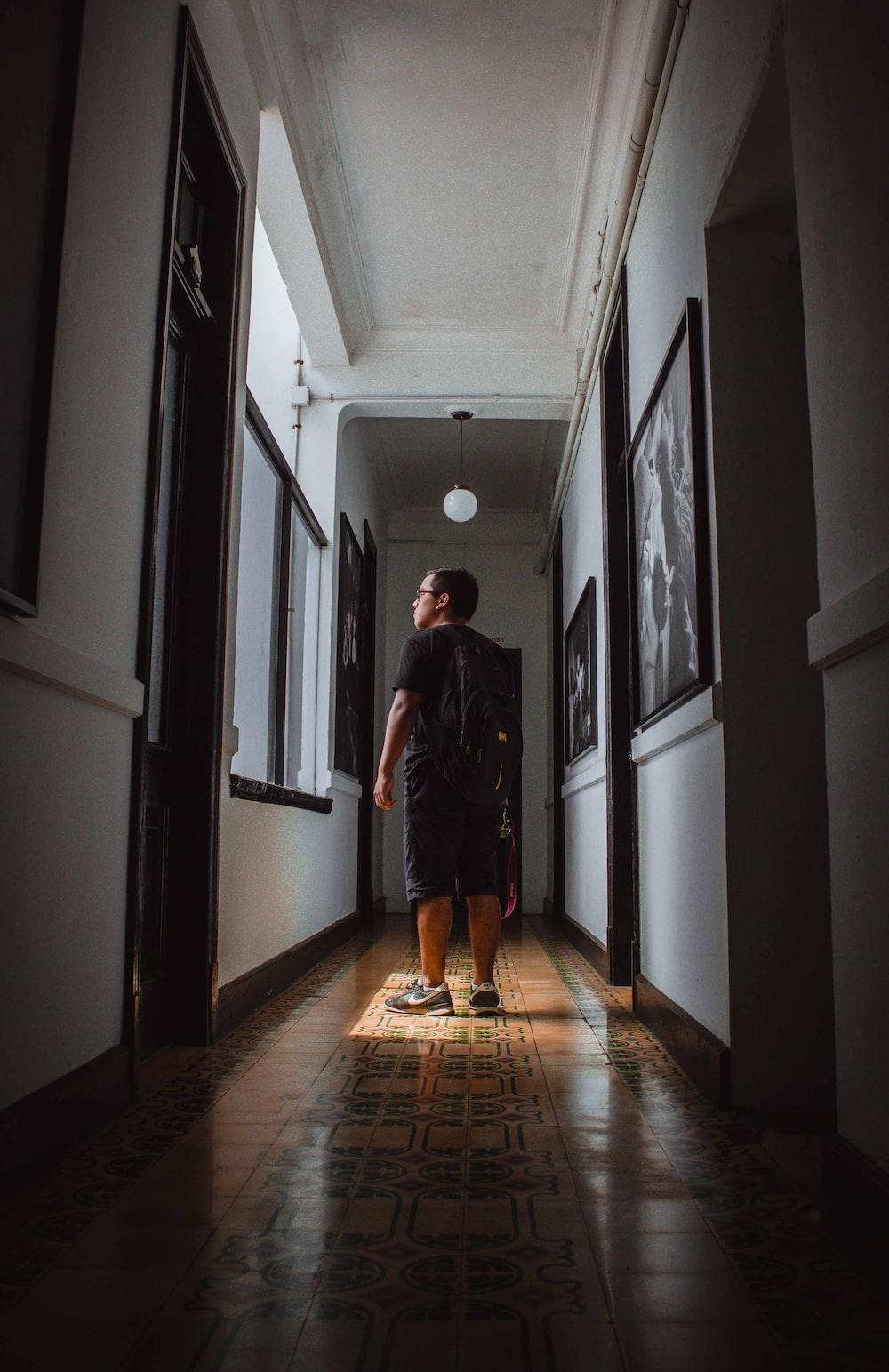 man in gray long sleeve shirt walking on hallway