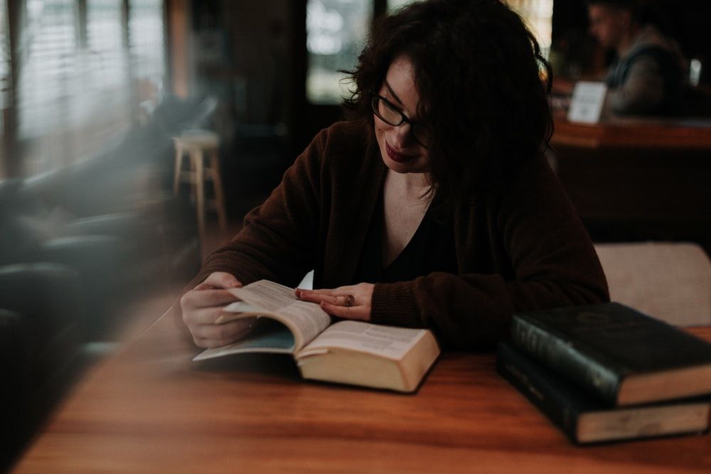 woman in brown long sleeve shirt reading book