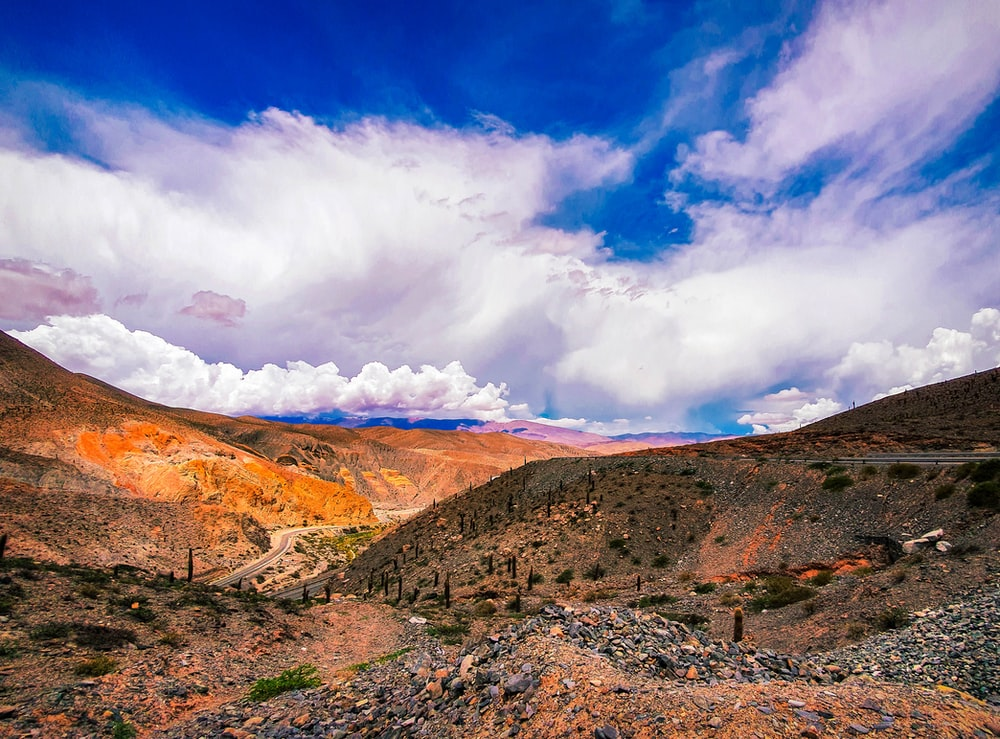 brown and green mountains under white clouds and blue sky during daytime