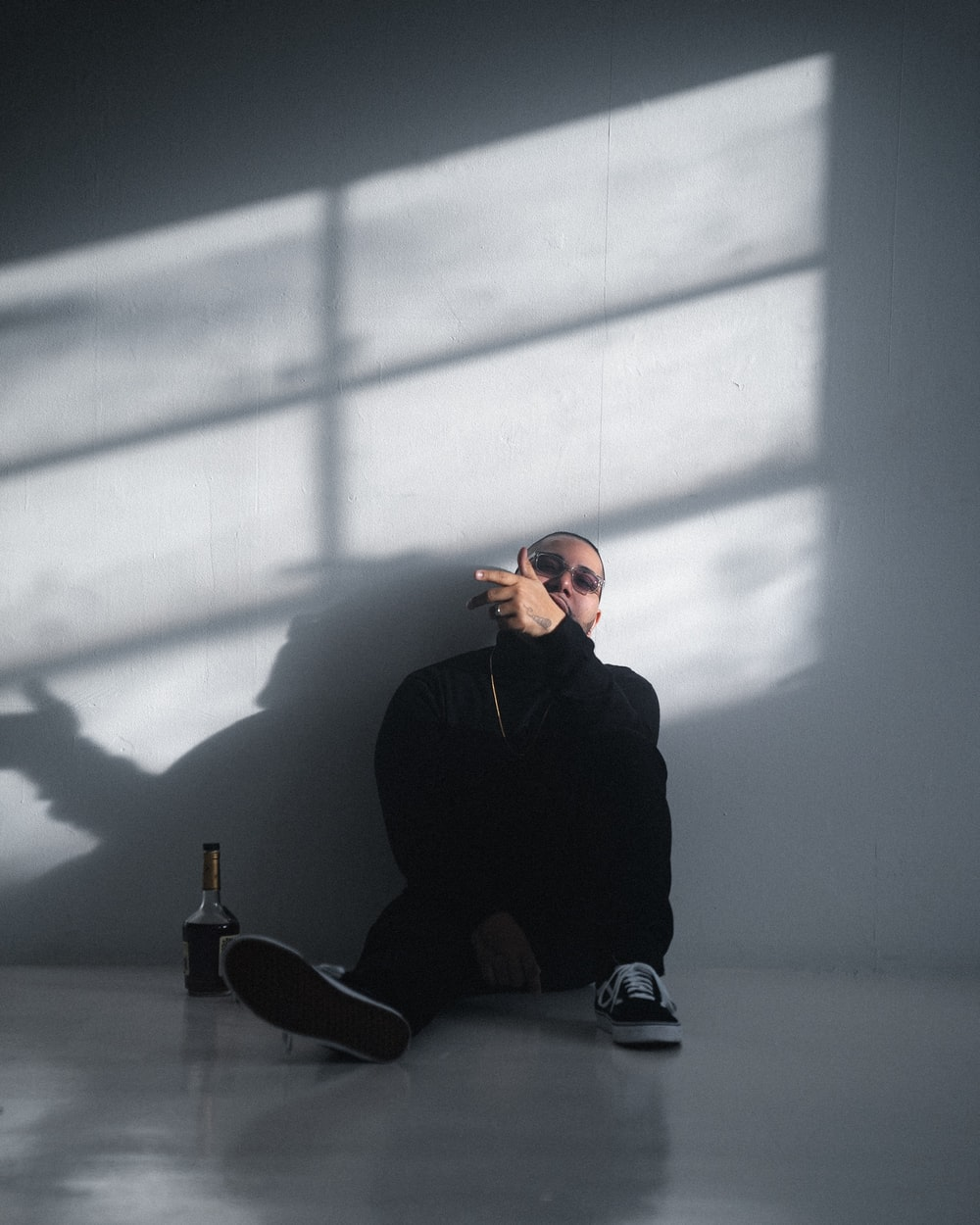 man in black long sleeve shirt and black pants sitting on floor