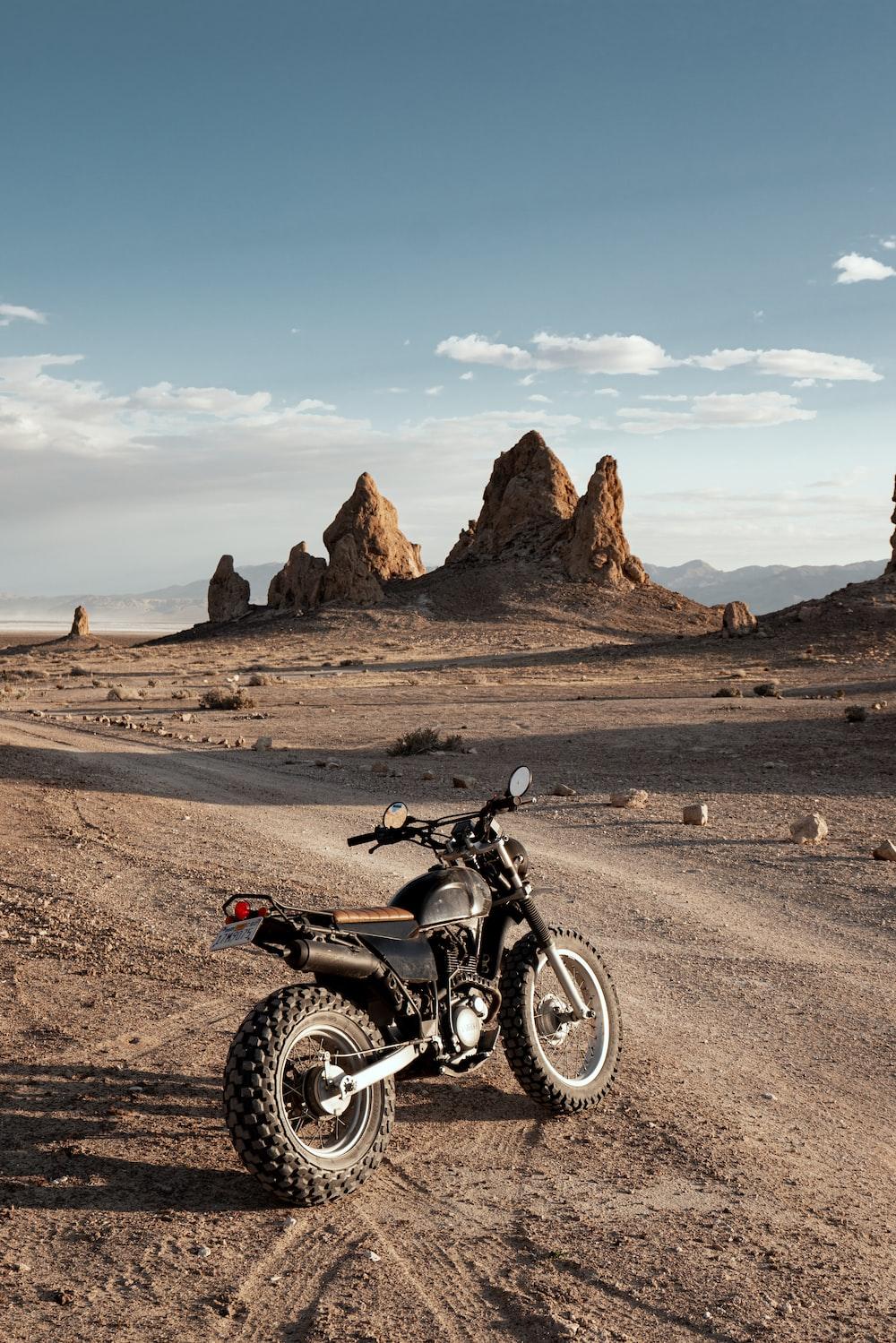 black motorcycle on brown dirt road during daytime