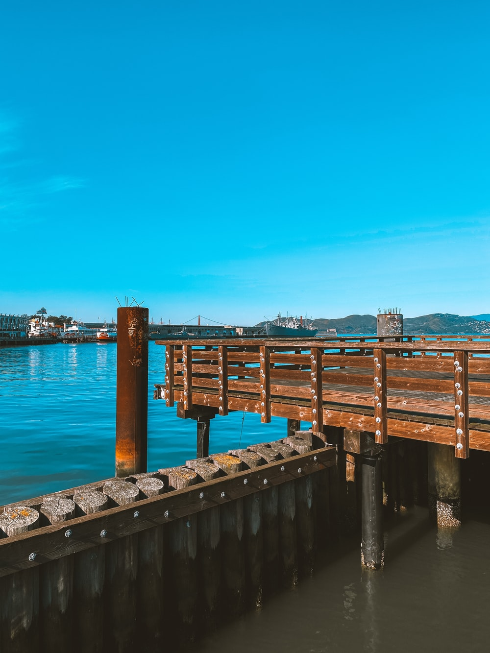 brown wooden dock on blue sea under blue sky during daytime