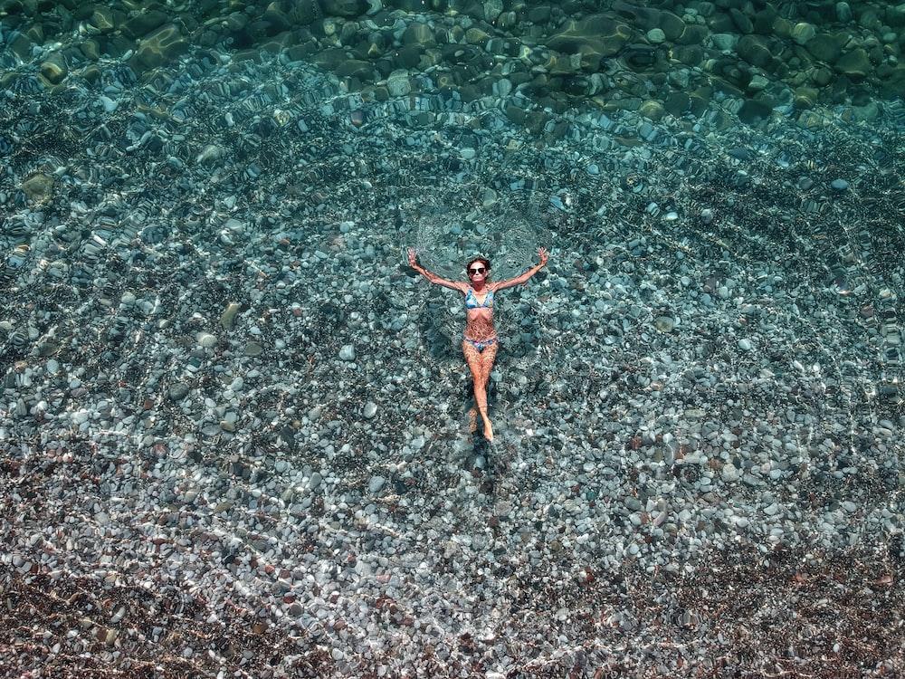 woman in red bikini swimming on water during daytime