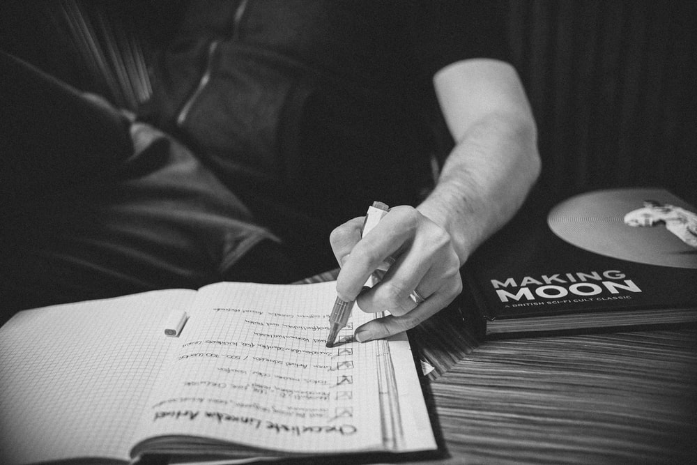 grayscale photo of person writing on paper