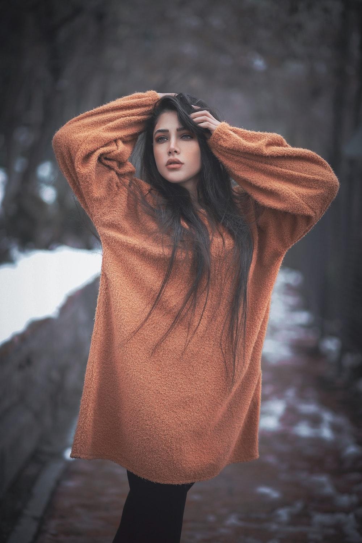 woman in orange hoodie standing near brown rock