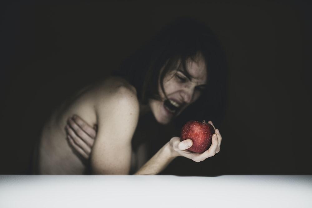 赤いリンゴを保持しているトップレスの女性