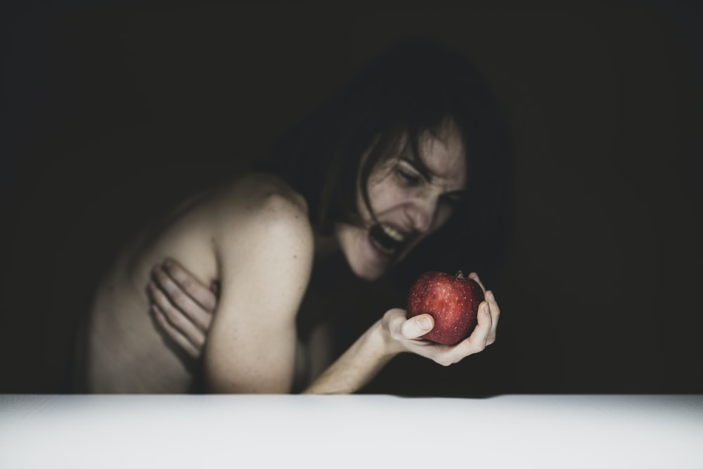 topless woman holding red apple