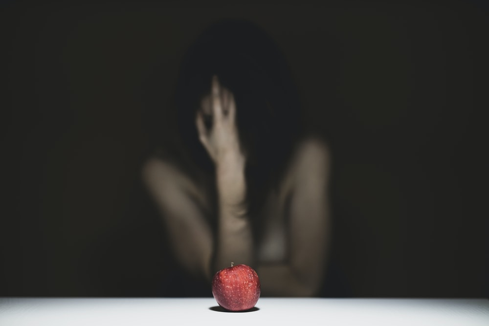 woman covering her face with red apple