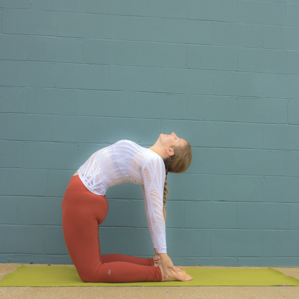 woman in white shirt and red pants bending her body on yellow yoga mat