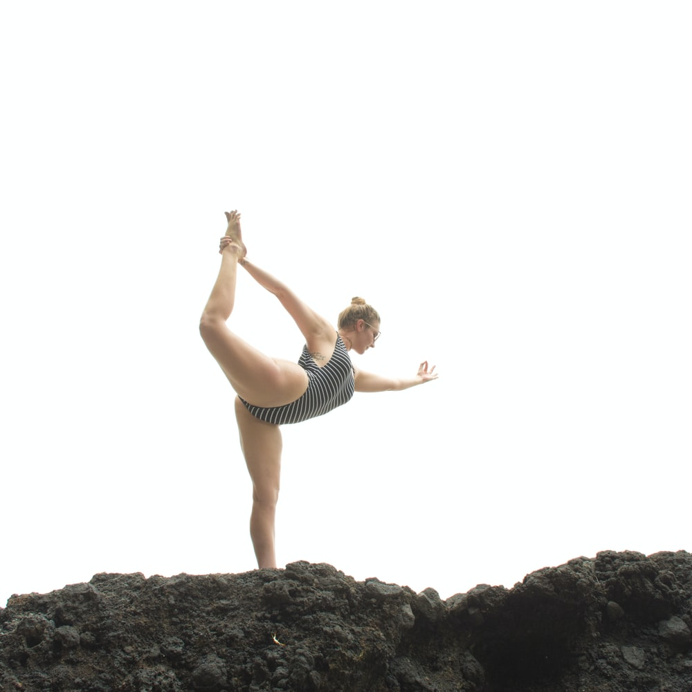 woman in black tank top and black shorts standing on rock during daytime