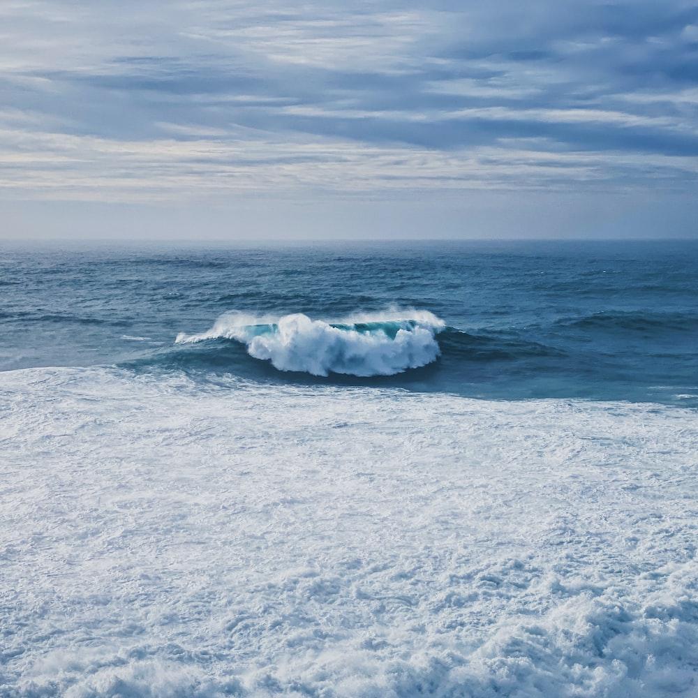 white sea waves on white sand during daytime