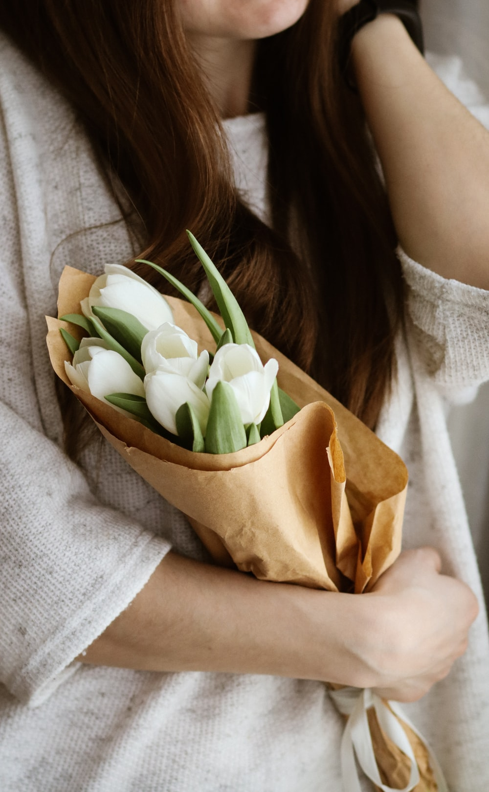 woman in white knit sweater holding white tulips bouquet